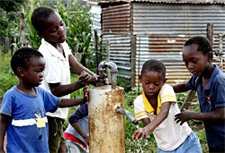The benefits of clean drinking water include improved sanitation and hygiene. Here, boys in Boikarabelo, South Africa wash their hands with water they pumped by playing on a PlayPump merry-go-round water pump. Photo: Frimmel Smith.