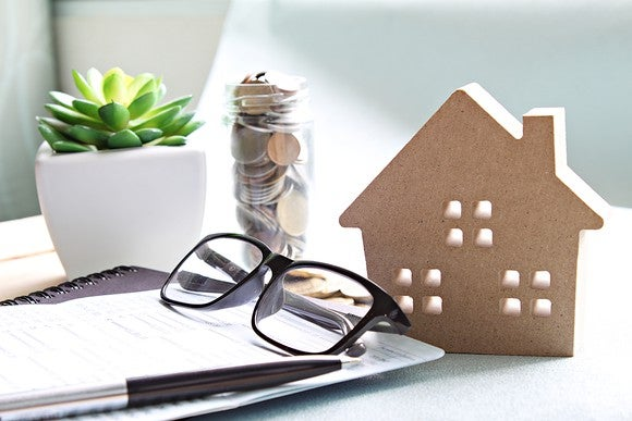 Miniature figurine of house next to glasses, pen, small jar of coins, and small potted succulent