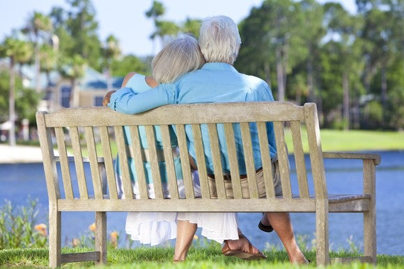 Senior couple sitting on a bench, overlooking a pond.