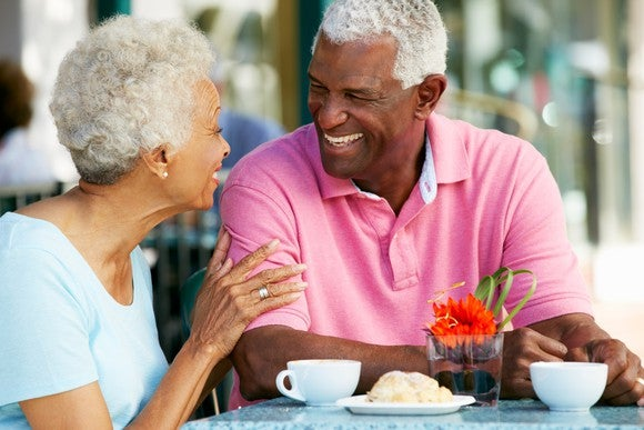 Elderly couple laughing while enjoying snack at cafe