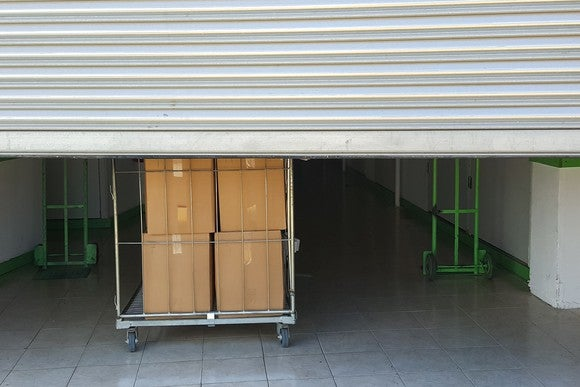 A storage unit with the door drawn halfway up where boxes can be seen inside.
