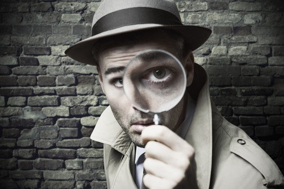 vintage-style detective in trenchcoat looking through a magnifier