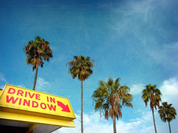 A sign pointing to the drive-in window with palm trees behind it