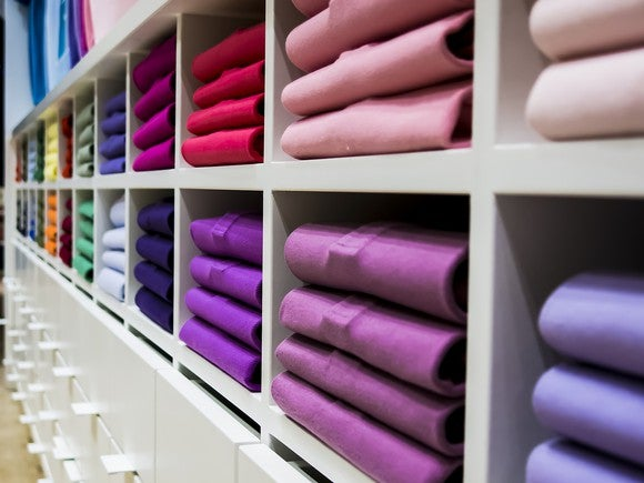 Folded piles of colorful t-shirts in display cubbies at a store