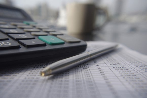 Calculator and pen sitting atop a financial statement with a coffee cup in the background