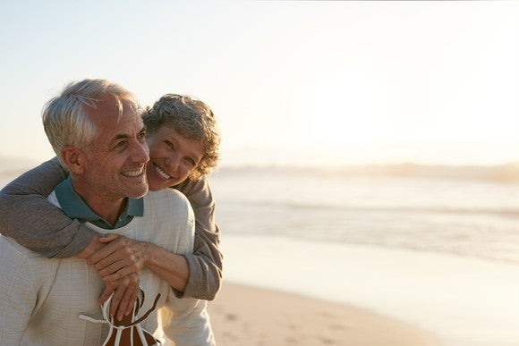 An older couple hugging on the beach.