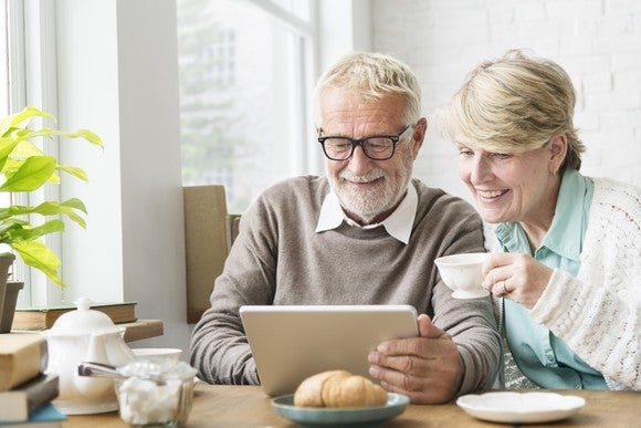 Two older people sitting at a table, drinking tea, and using a tablet.