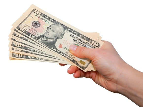 A hand holding a group of fanned out $10 bills.