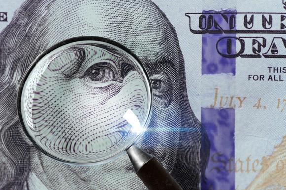 A 100 U.S. bill under a magnifying glass