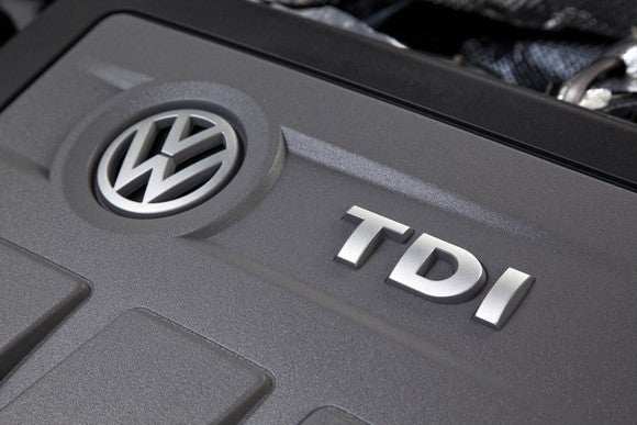 "A closeup of the engine cover on a 2.0-liter VW turbodiesel engine, showing the VW brand logo and the initials ""TDI"""