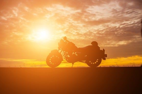 A motorcycle parked with a sunset behind it.