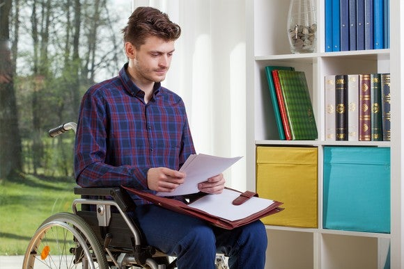 Man in wheelchair looking at papers