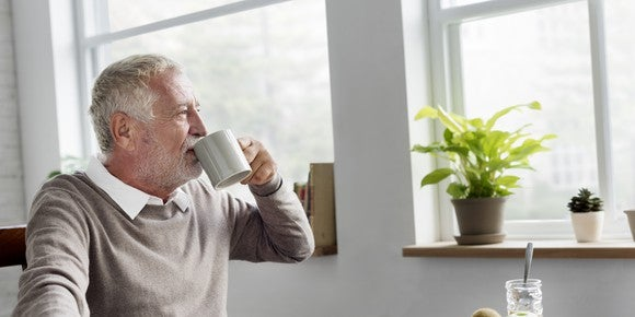 And older person sitting at a table, drinking coffee, and looking out the window.