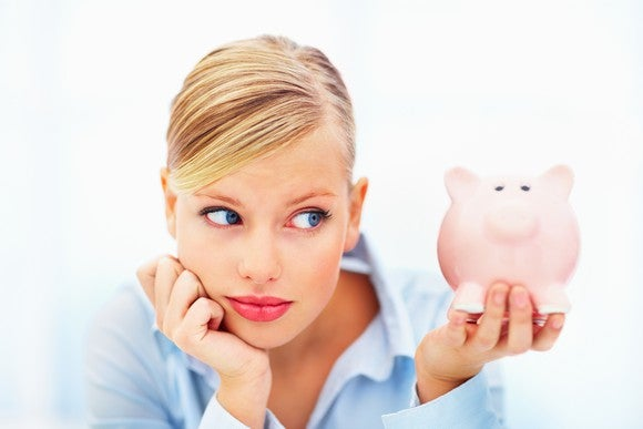 Worried Millennial Woman Holding Piggy Bank Getty