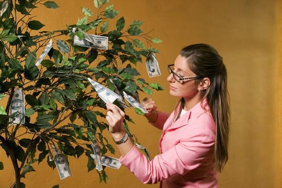 Woman Picking Money Tree Getty