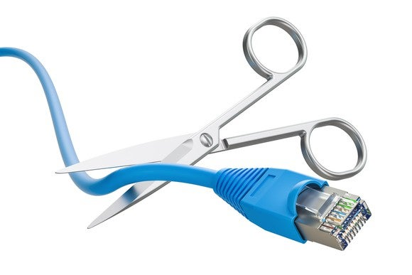 A pair of scissors cutting a blue ethernet cord.