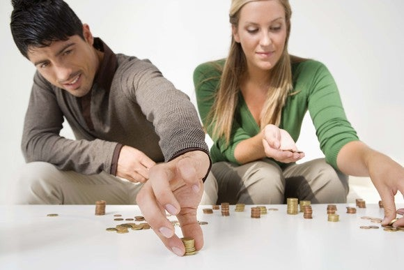 Couple Counting Coins And Saving Money Budgeting Getty