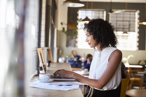 A businesswoman works at a laptop by the window in a coffeeshop.