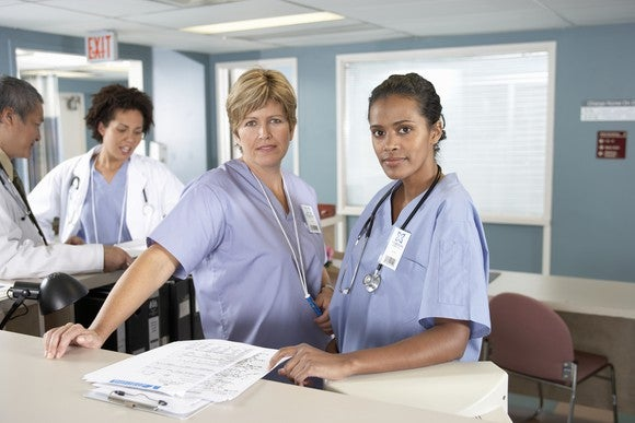 Nurses And Doctors At Reception Desk Getty