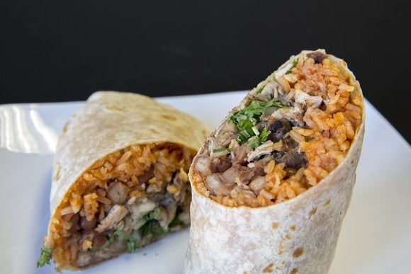 A burrito cut in half on a plate.