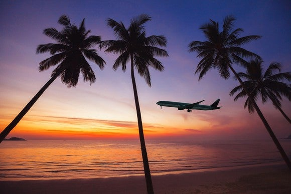 An airplane silhouetted against a tropical sky at sunset, with palms in the foreground