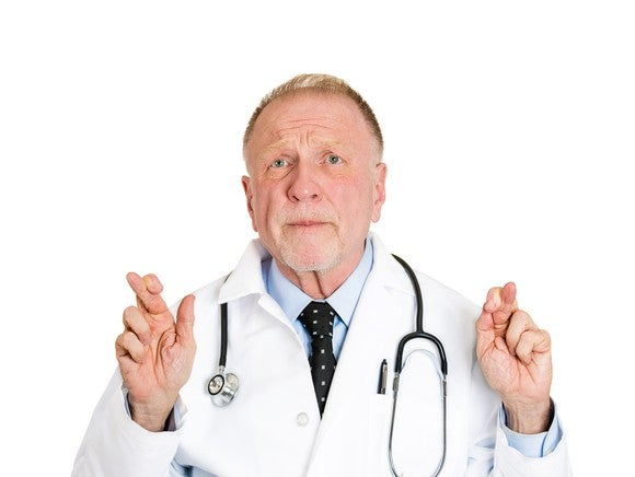 Doctor Crossing Fingers Obamacare Getty