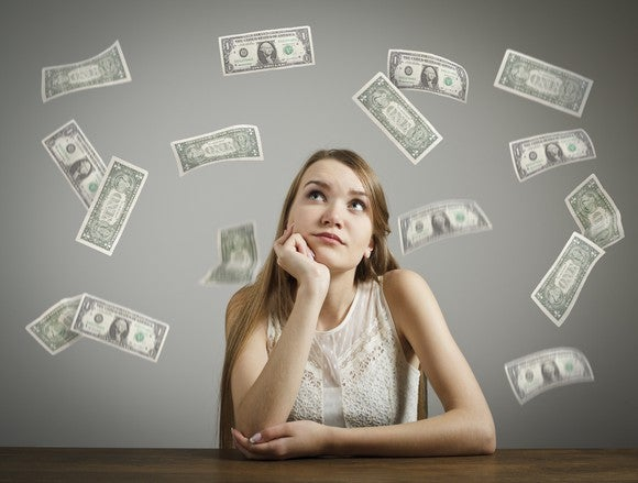 Young Adult Woman Looking At Dollar Bills Getty
