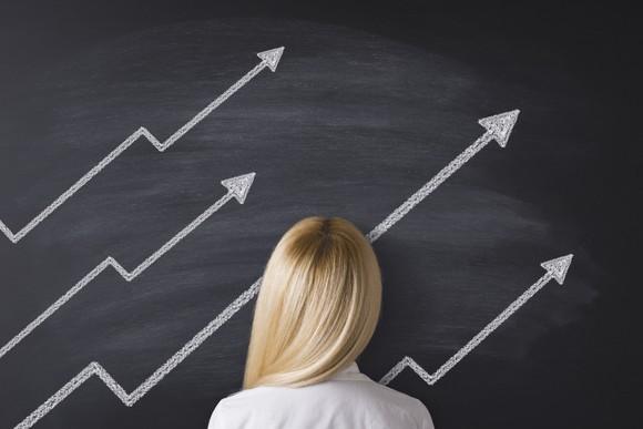 Getty Images Woman Blackboard Explaining Stock Rises