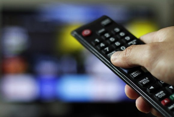 Hand holding a remote control in the foreground; blurred screen in background