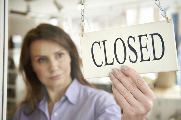 Woman With Closed Sign On Shop Door Getty