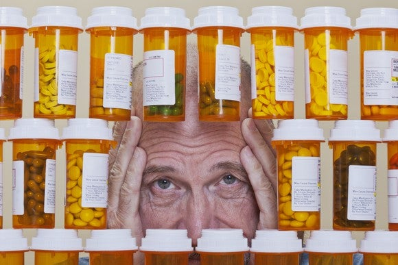 Senior Looking Through Prescription Medicine Getty