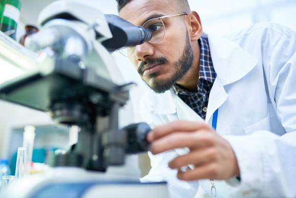 Man in lap coat looking through a microscope