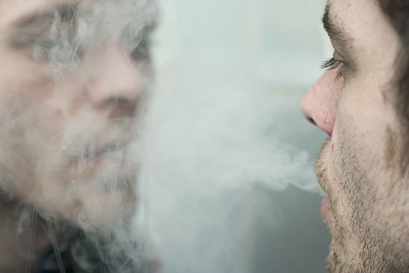 Man Blowing Smoke Into Mirror Reflection Getty