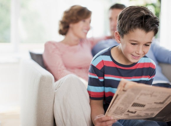 Getty Kid Reading Newspaper Investing Stocks