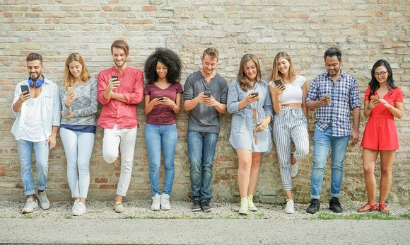 Nine young people leaning against a wall, all looking at their smartphones