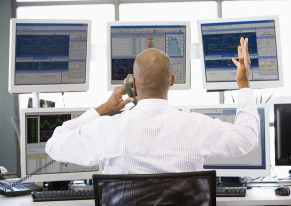 Stock Trader Talking On Phone In Front Of Chart Screens Getty