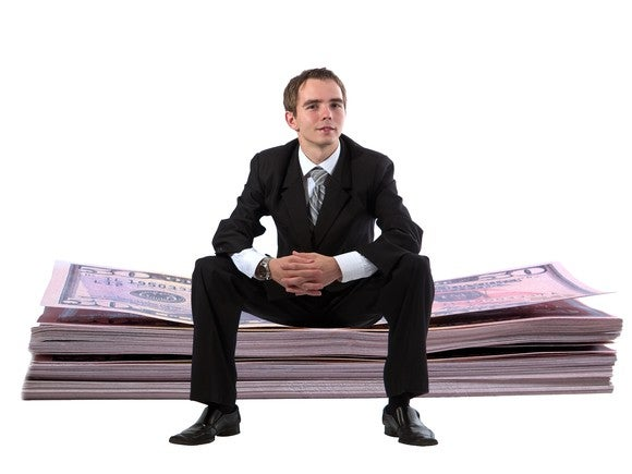 Young Man Sitting On Stack Of Cash Getty