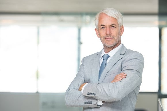Baby Boomer Ceo In Suit Smiling Arms Crossed Getty