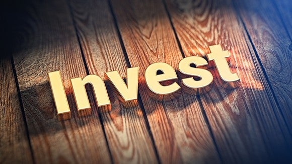 """The word """"Invest"""" written in gold sitting atop wooden boards."""