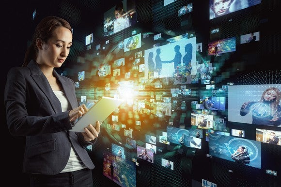 A woman with a tablet stands in front of a bank of virtual TV screens.