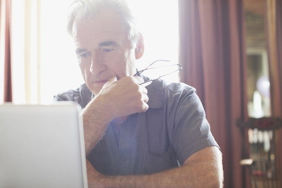 A senior man stares pensively at a laptop computer displaying Medicare premium rates.