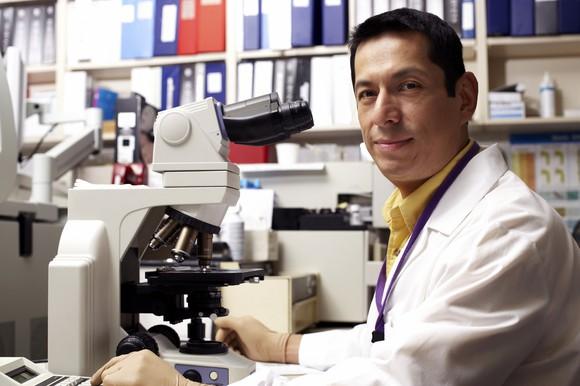 Lab Researcher Portrait Using Microscope Getty