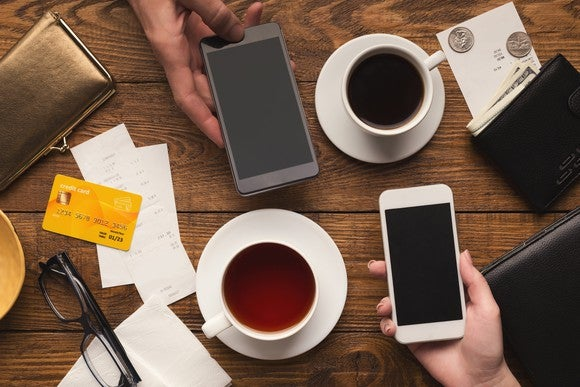 Phones and coffee cups on a table with bank cards visible.