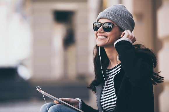 Woman listening to music on tablet via headphones