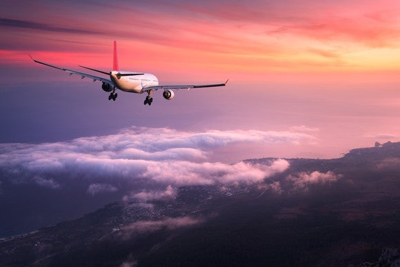 A plane flying high over a city against a pink and yellow sky.