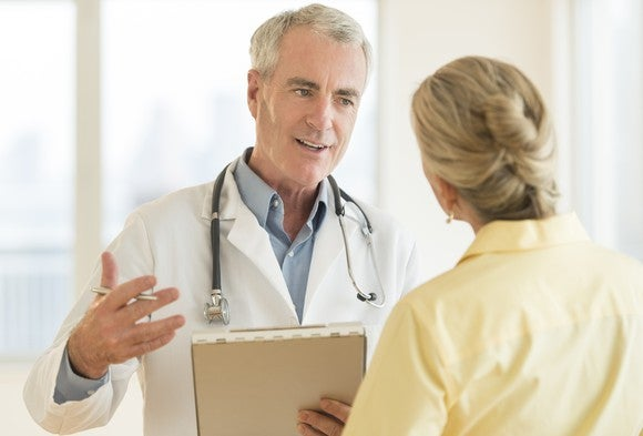 Doctor Discussing Report With Patient Clipboard Getty