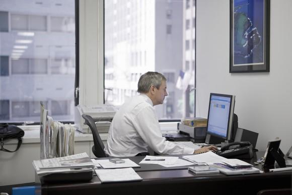 Older Man Working At Desk