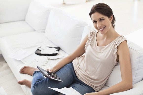 Young Woman Budget Paying Bills With Calculator Getty