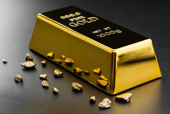 Gold Bar With Nuggets On Dark Background Getty