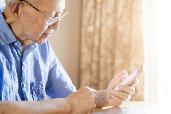 Older man looking pensive, holding a phone